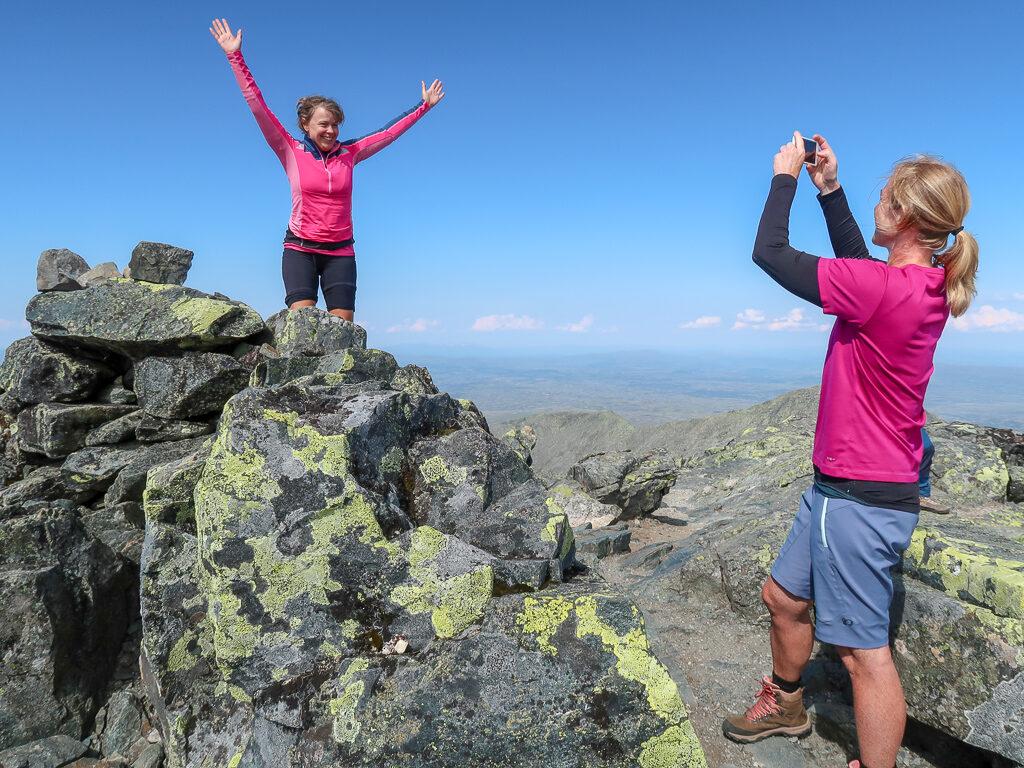 Glad kvinna på toppen av Storsylen.
